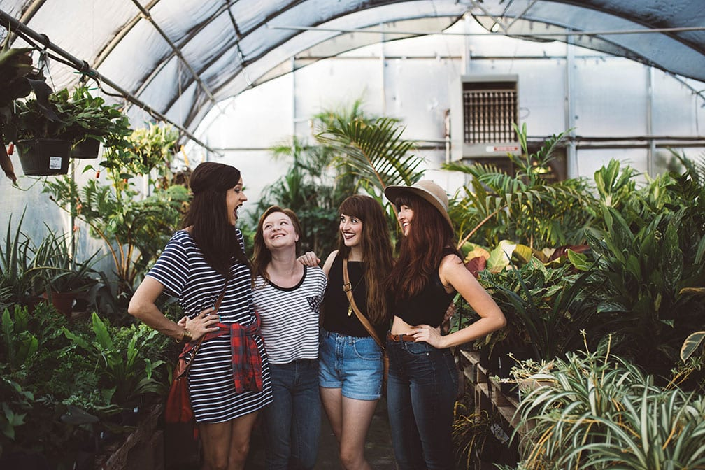friends girlfriends greenhouse plants laughing girls trip road trip four group