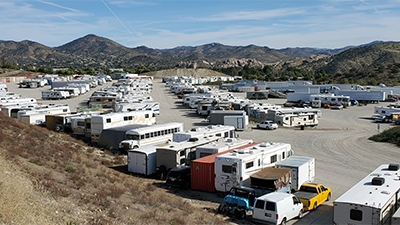 cars trucks RVs and shipping containers on a large sand lot