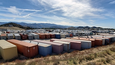 multiple color shipping containers stored on a large lot