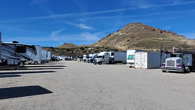 RVs 18 wheelers and shipping containers on a lot