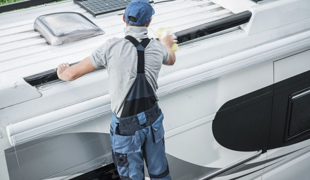 man cleaning and maintaining an RV