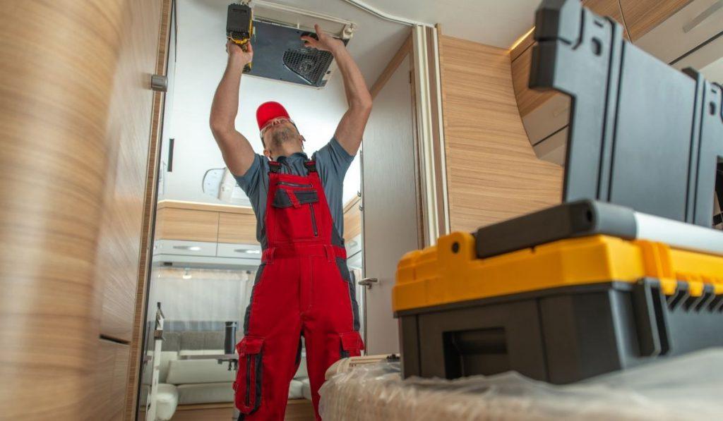 RV technician repairs air conditioner